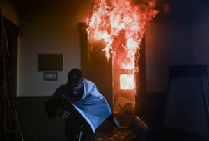 A demonstrator runs after setting fire to an office in the Congress building during a protest demanding the resignation of President Alejandro Giammattei.