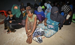 Migrants seated on dusty floor