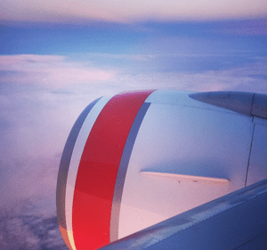 View out of airplane window on to clouds at sunset