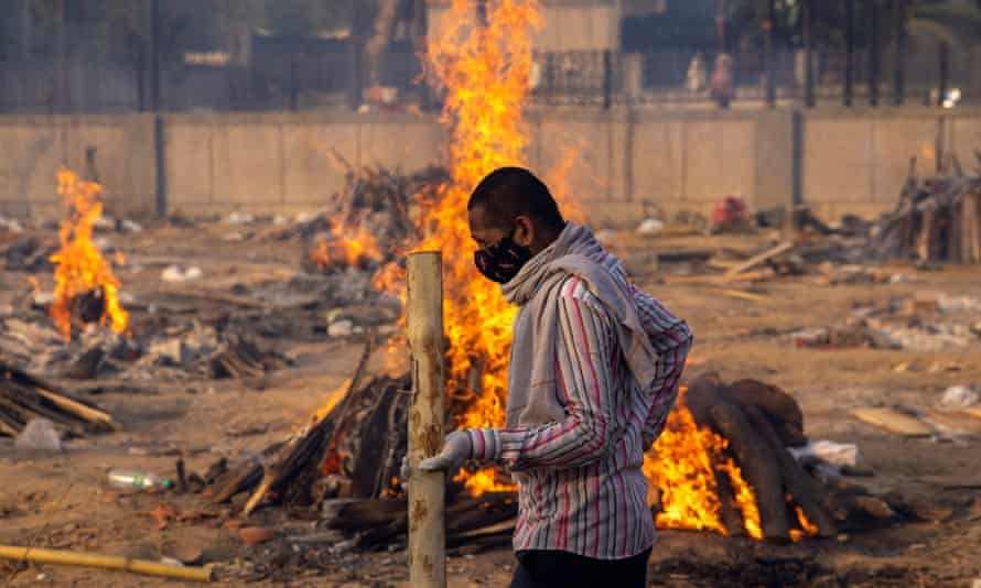 A man walks past burning funeral pyres of people, who died from Covid.