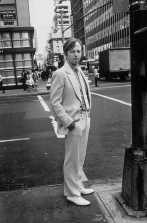 Tom Wolfe pictured in his signature white suit and shoes on a street corner in New York in 1968.