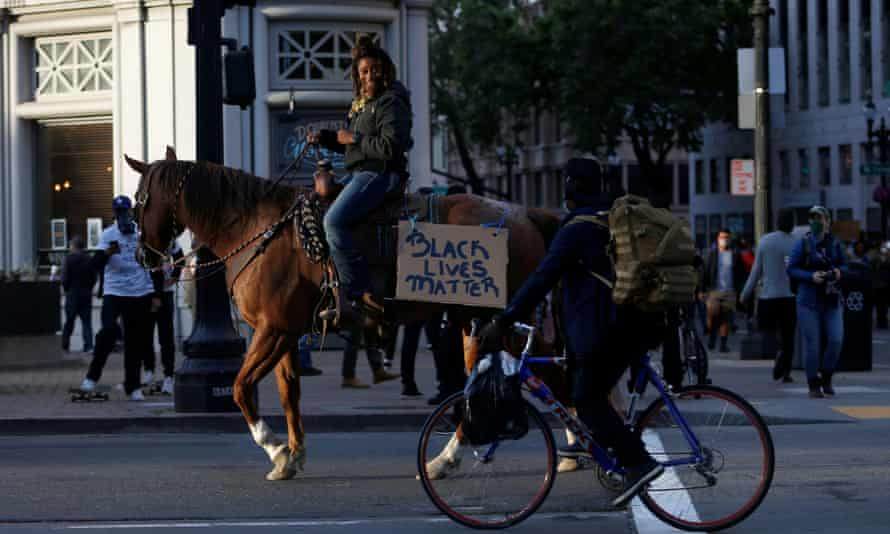 Brianna Noble takes part in the protest against the death of George Floyd in Oakland, California, with Dapper Dan, her horse.