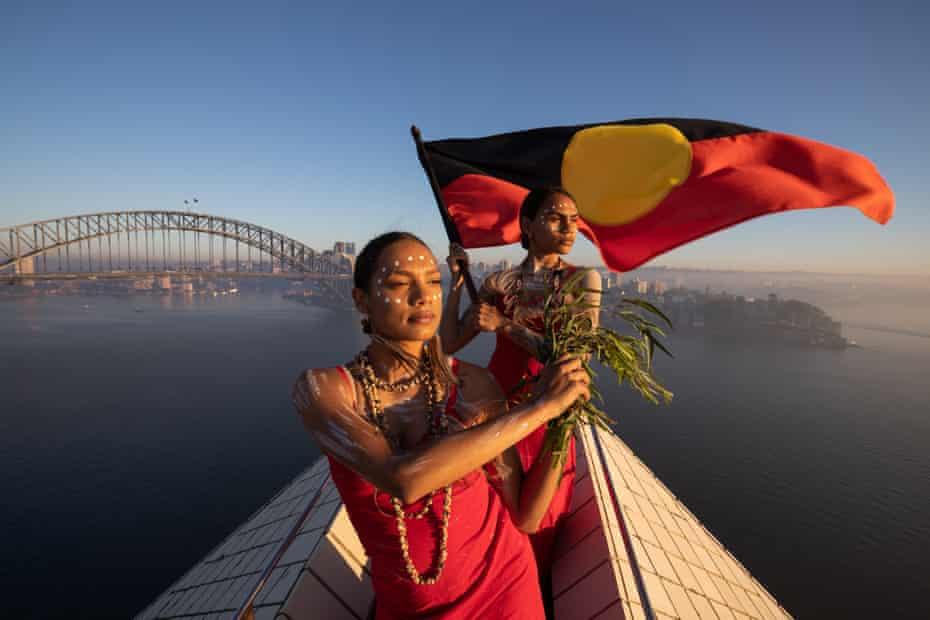 Dharpaloco (Dubs) Yunupingu and Abigail Delaney from Jannawi Dance Clan fly the Aboriginal flag atop the Sydney Opera House in 2019