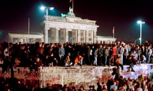 Thousands of East Berliners crowd atop the Berlin Wall, near the Brandenburg Gate