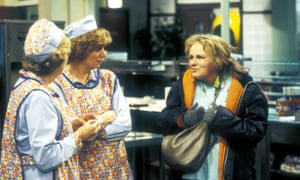 A scene from Dinnerladies (l-r): Anne Reid and Victoria Wood in overall and caps, and Julie Walters in a large puffy raincoat