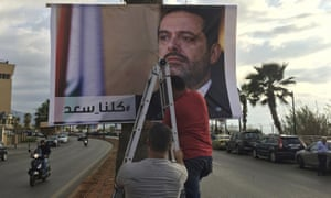Workers hang a poster of outgoing prime minister Saad Hariri with the Arabic words 'We are all Saad' in Beirut.