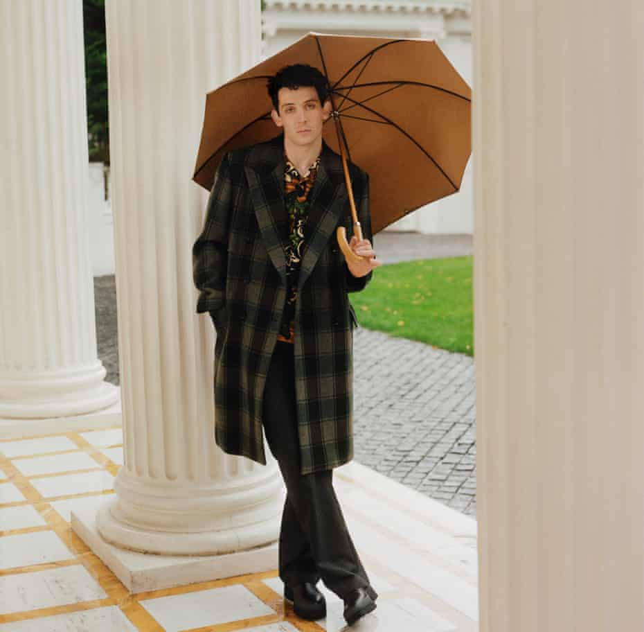 Actor Josh O'Connor standing among pillars at a stately home, holding an umbrella over his head