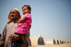 Mohammed holds his grand daughter in front of a row of now-empty tents at a camp in northern Iraq