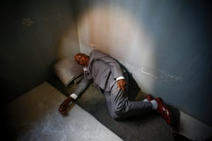 The former political prisoner demonstrates how he used to sleep during the launch of the replica of Nelson Mandela's Robben Island prison cell in 2016.
