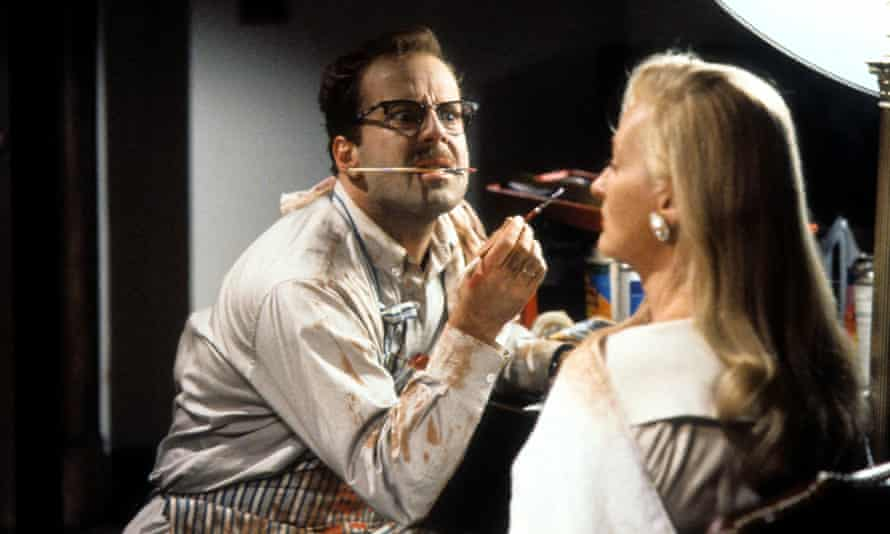 Bruce Willis painting Meryl Streep's face in a scene from the film Death Becomes Her, 1992.