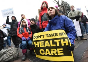 Brandy Mello holds a sign during a rally in support of the Affordable Care Act in Denver, Colorado.