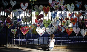 DOUNIAMAG-BRITAIN-FIRE-CARNIVAL-LIFESTYLEA young girl adds finishing touches to paper hearts adorning a fence in Kensington, near the burnt-out remains of Grenfell Tower in London on August 25, 2017 ahead of the Notting Hill Carnival. The art work is being made by volunteers from the community devestated by the Grenfell tower fire disaster as part of a project called Green for Grenfell in which paper hearts, banners, posters and bunting relating to the Grenfell tower tragedy are being made out of recycled materials to adorn the streets in time for the Notting Hill Carnival this coming weekend. / AFP PHOTO / Tolga AKMEN (Photo credit should read TOLGA AKMEN/AFP/Getty Images)