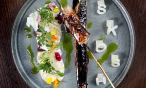 """Barbecued strips of mackerel and eel on skewers with a decorative sauce/salad one side of the plate and the letters """"SKOSH' cut out in kohlrabi on the other"""