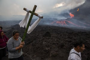 San Vicente Pacaya, GuatemalaA woman carries a wooden cross during a pilgrimage to pray that the Pacaya volcano decreases its activity