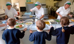 Children being served lunch by dinner ladies