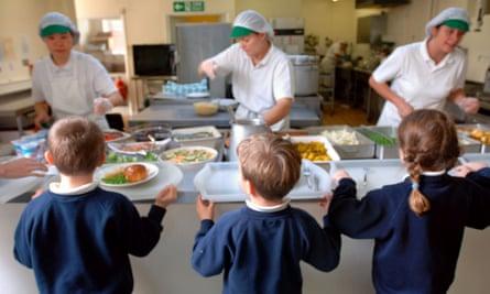 Schoolchildren waiting to be served by dinner ladies