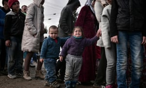 Refugees and migrants queue for food at a makeshift camp near Idomeni