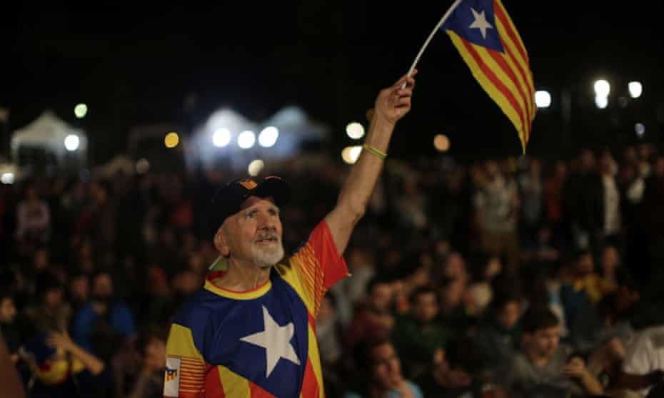 A man waves an estelada, or Catalonia independence flag, during a gathering at Plaza Catalonia in Barcelona on the day of the referendum