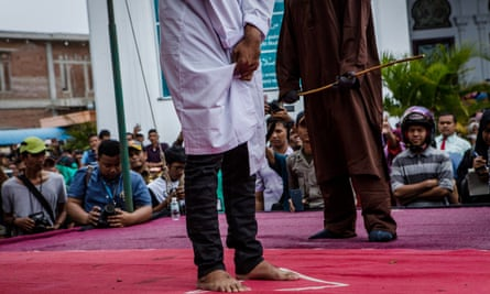 A crowd gathers to watch as a young Indonesian man prepares to be caned on 23 May.