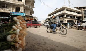 A man rides a motorcycle in the north-western Syrian city of Idlib on the first day of a Turkey-Russia ceasefire.