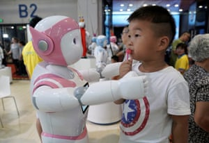 A boy plays with a robot in Beijing