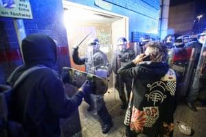 Demonstrators confront police officers.