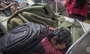 The son of a patient affected by cancer sleeps besides his father inside one of the rooms at the Bhaktapur Cancer Hospital on February 02, 2015 in Bhaktapur, Nepal.
