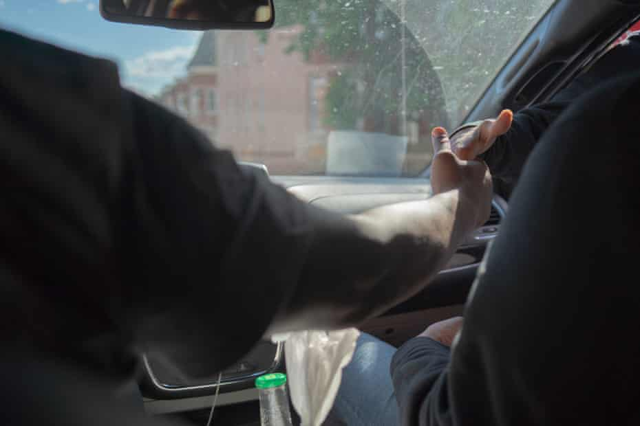 Jamal West shakes hands with one of his clients, a young man who deals drugs on a corner in West Baltimore.