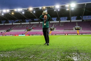 Referee Szymon Marciniak inspects the pitch.