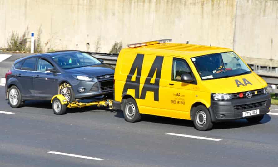 Ford car being towed along M25 motorway by AA breakdown van