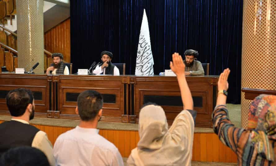 Female reporters try to question the Taliban's Zabihullah Mujahid at a press conference in Kabul just after the Islamists' takeover