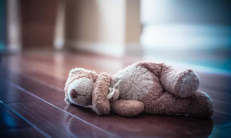 Forlorn old worn teddy bear left in empty room.