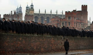 Etonians sit on a boundary wall at Eton College