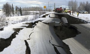 A tow truck holds a car pulled from on an off-ramp that collapsed during a morning earthquake in Alaska