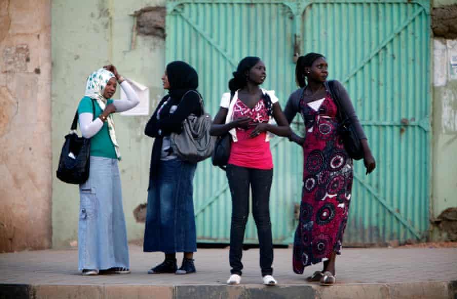 Women wait for public transport in Khartoum in 2012