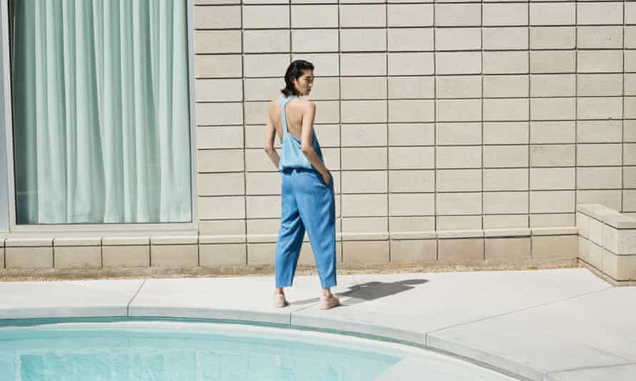 A model in three-quarter length jeans and a skimpy vest, standing, hands in pockets, with her back to a pool