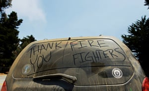Thank You Firefighters is written on the dust covered rear window of a vehicle