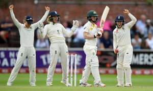 Rachael Haynes of Australia stands dejected as the England players celebrate her wicket.