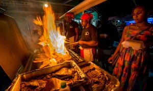 Cooks frying up fish on a BBQ at Oistins fish fry night, Barbados