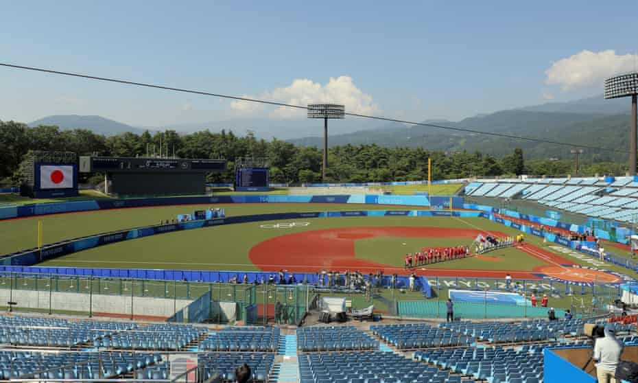 Japan  and Australia's softball teams line up in front of spectator-less stands ahead of their match at the  Fukushima Azuma Baseball Stadium