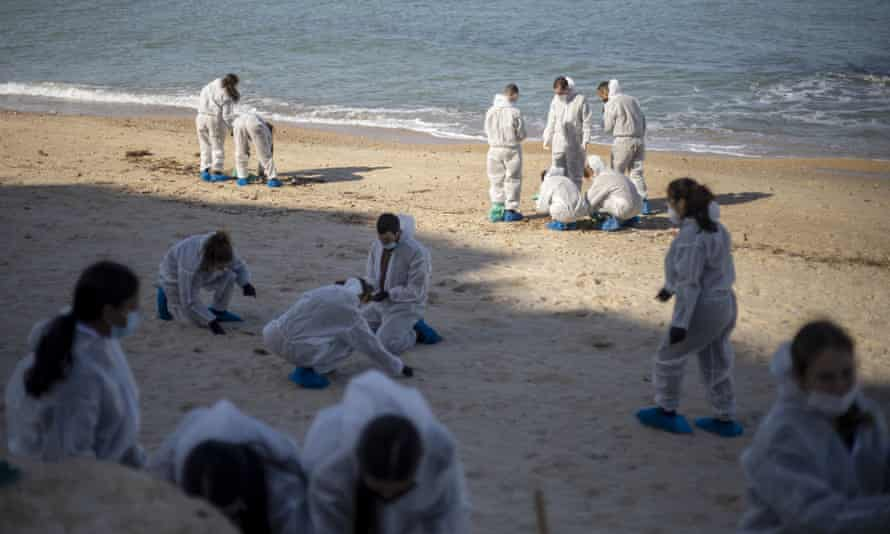 Israeli soldiers in protective suits clean tar from a beach after an oil spill in the Mediterranean near Ga'ash, Israel.