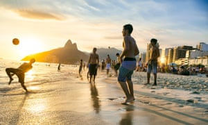 Young Brazilian men play keepy uppy on the beach