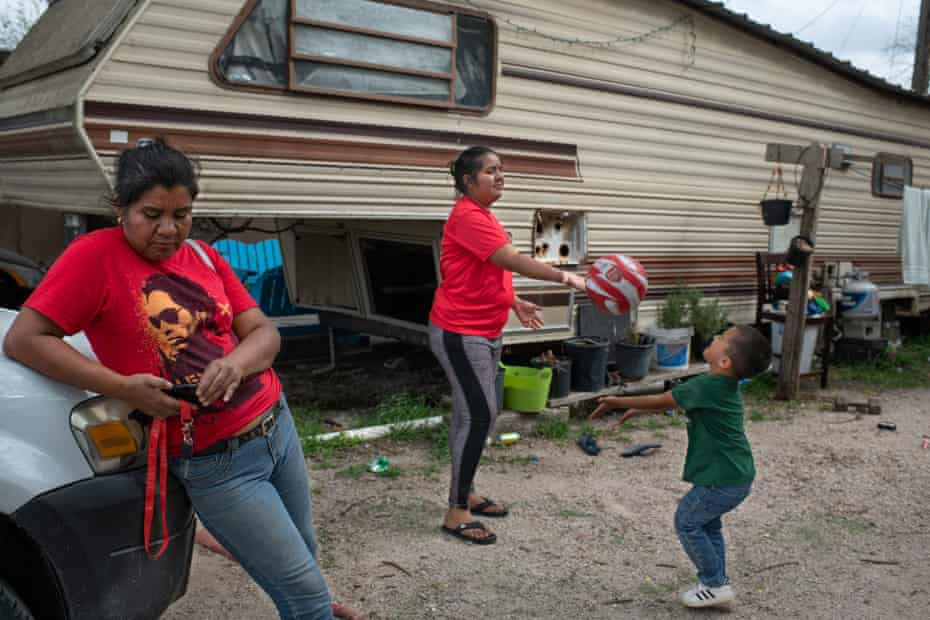 Irene returns from working in the fields, while her daughter, Kori, plays with her son in front of their house.