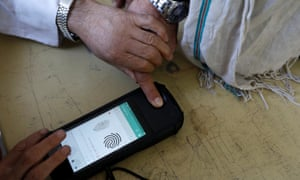 An election official scans a voter's finger with a biometric device at a polling station in Kabul