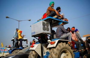 Farmers sit on a tractor as they listen to a speaker during a protest