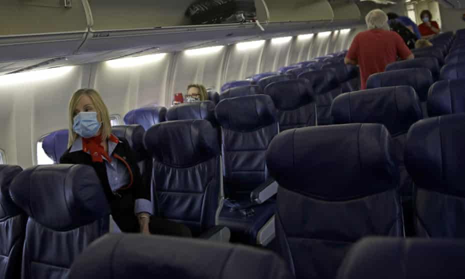 A Southwest Airlines flight attendant waits at left, as the final passengers board a plane.