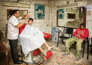 The Barbershop, Havana, Cuba, by Roy Morris 'Walking through the grubby back streets of Havana,' says Morris, 'I chanced upon this very old and scruffy barbershop. Standing in the doorway I could see the barber, his young customer and a man wearing a jumper with HAPPY on it, though he looked really miserable. The old Cuban revolutionary pictures on the wall sealed the image in the 1950s for me.'