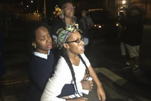 Carroll Fife, regional director of Alliance of Californians for Community Empowerment, left, holds back Walker, distraught over the arrests of her former housemates on Tuesday.