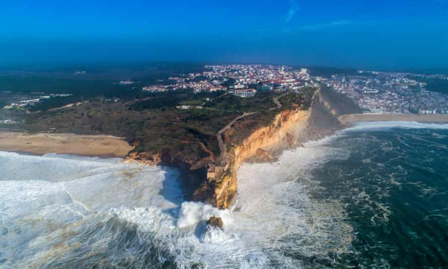 'Way beyond all other waves': Nazaré's lighthouse at Praia do Norte acts as a grandstand for spectators.
