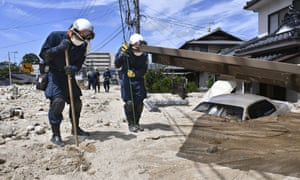 Police search around a house buried in sand and mud after torrential rain in Hiroshima prefecture.